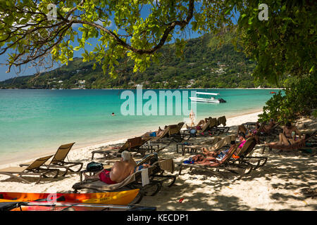 The Seychelles, Mahe, Beau Vallon, beach, tourists on sun loungers outside H Resort - Stock Photo