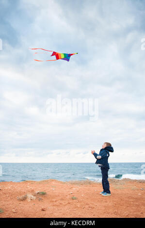 cute small caucasian boy wearing autumn jacket playing flying kite standing on the shore near stormy sea
