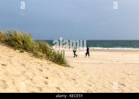 SAND DUNES AT BOURNEMOUTH BEACH. A MAN AND WOMAN WALK ALONG THE WATERS EDGE AT BOURNEMOUTH