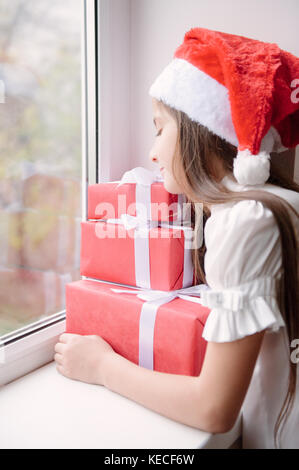 nice little girl in santa hat dreaming by the window hugging christmas gifts stock photo - Nice Christmas Gifts