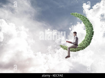 Handsome student guy sitting on green moon and reading book - Stock Photo