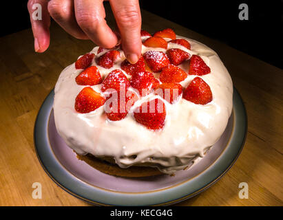 A woman's fingers putting in place the final strawberry on top of a cream topped, sponge birthday cake with strawberries. - Stock Photo