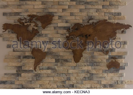Handmade wooden map of the world on the wall with bricks - Stock Photo