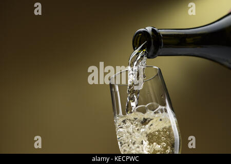 Pouring white wine from a bottle into a wineglass: celebration and wine tasting - Stock Photo