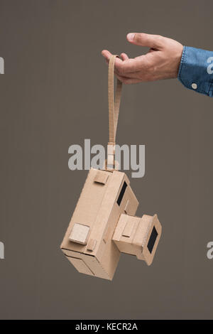 Photographer holding an handmade eco-friendly cardboard camera, crafts and creativity concept - Stock Photo