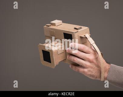Photographer holding an handmade cardboard camera, crafts and creativity concept - Stock Photo