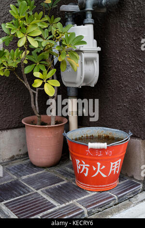 Kyoto, Japan -  May 23, 2017: Traditional red fire bucket with water in front of the house as fire prevention in Kyoto