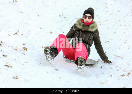Beautiful caucasian girl laughing and having fun riding a saucer sled downhill in a forest or city park. - Stock Photo