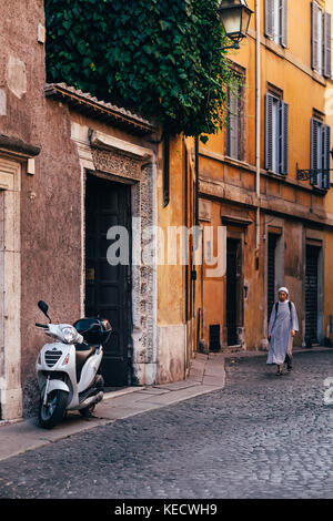 A nun walks down a sunlit street towards a parked scooter in Rome, Italy, where catholic nuns are a common sight through the city