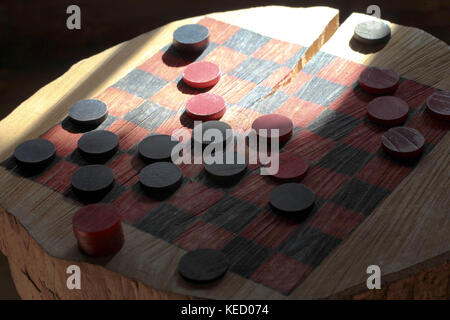 An old fashion checkers board game set up on a tree stump in a log cabin in Michigan - Stock Photo