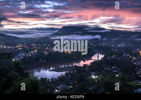 Sun beginning to rise over Luang Prabang, Northern Laos. - Stock Photo