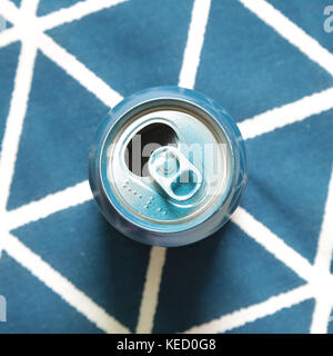 Empty can on blue fabric background - Stock Photo