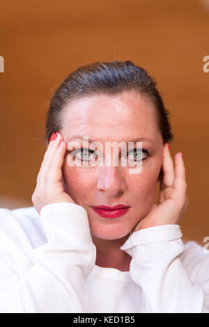 Portrait of a middle aged woman suffering from headaches in her attic apartment. - Stock Photo