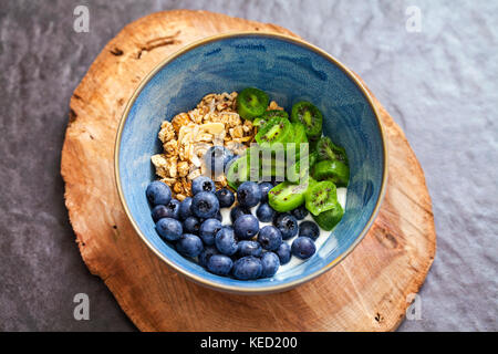 Yogurt with kiwi berries, blueberries and granola - Stock Photo