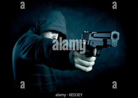 Hooded man with a gun in the dark - Stock Photo