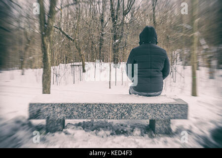 Man sitting on bench in a forest in winter with snow on the ground - Stock Photo
