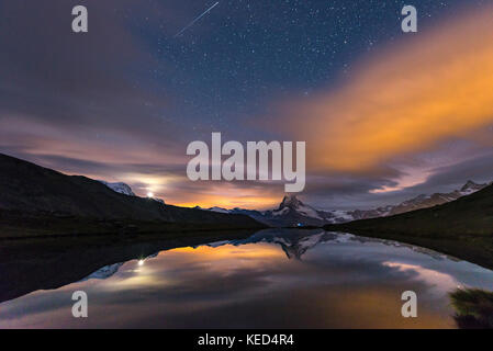 Night view, starry sky with shooting star, snow-covered Matterhorn reflected in the Sellisee, Valais, Switzerland - Stock Photo