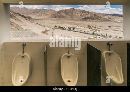 A view towards the valley and mountains through a lavatory window in Ladakh, India - Stock Photo