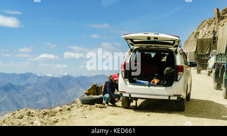 A man changing a tyre on the highest navigable road at Khardungla Top, Ladakh, India at 18380 feet above sea level - Stock Photo