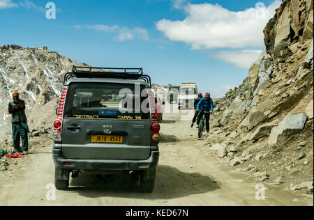 Cyclists and workers mingle on the highest navigable road at Khardungla Top, Ladakh, India at 18380 feet above sea - Stock Photo