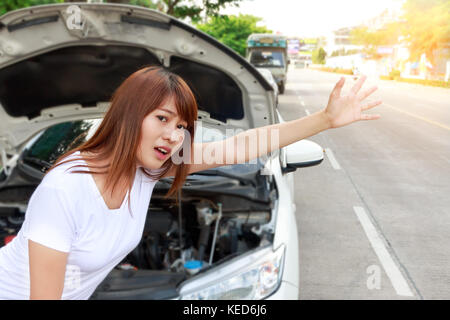 Woman looking for help after a car breakdown, standing besides car and hitching a ride. - Stock Photo
