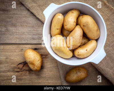 Composition of fresh organic potatoes in white ceramic bowl on hemp sake and   rustic wooden table. Preparation - Stock Photo