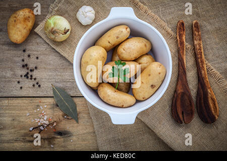 Fresh organic potatoes in white ceramic bowl with ingredients and herbs  , parsley, garlic, bay leaves, pepper, - Stock Photo