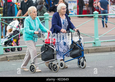 Elderly women crossing a road with wheeled walkers in Brighton, East Sussex, England, UK. Zimmer frame. Rollator. - Stock Photo