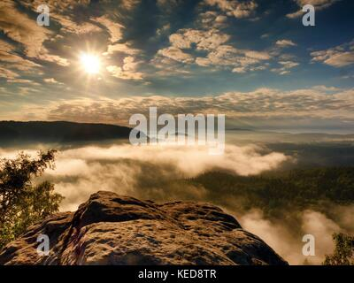 Landscape view. Exposed sandstone cliff above deep misty valley in Saxony Switzerland. Dreamy mood within daybreak - Stock Photo
