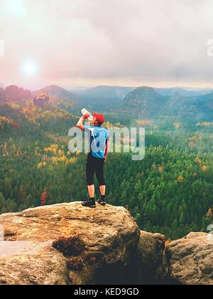 Thirsty hiker in blue and black sportswear drinking water from plastic bottle. Sweaty tired tourist on the peak - Stock Photo