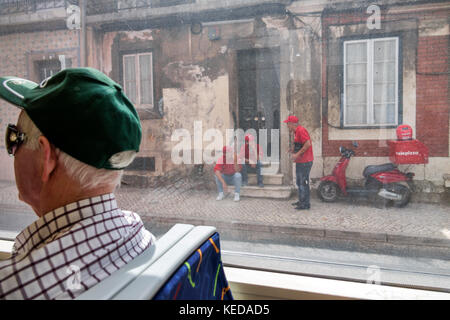 Lisbon Portugal Carris Tram 15 Belem route public transportation man sitting view through window passenger rider - Stock Photo