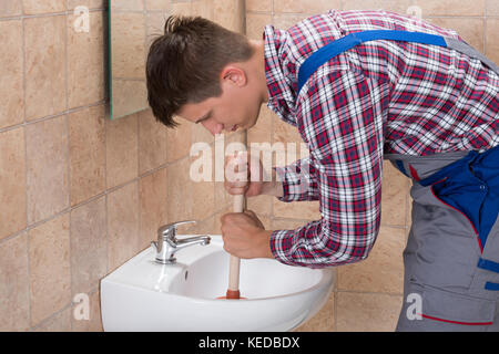 Close-up Of A Plumber Using Plunger In Bathroom Sink - Stock Photo