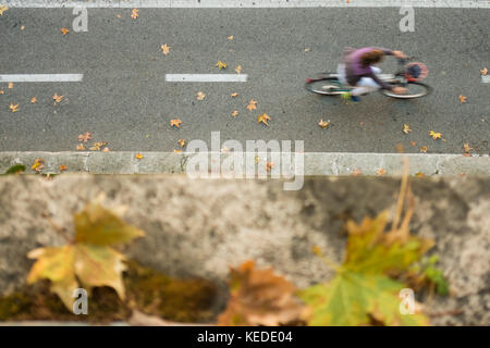 -Selective Focus- View from above, defocused/blurred person with a yellow t-shirt  is running on a pedestrian track. - Stock Photo