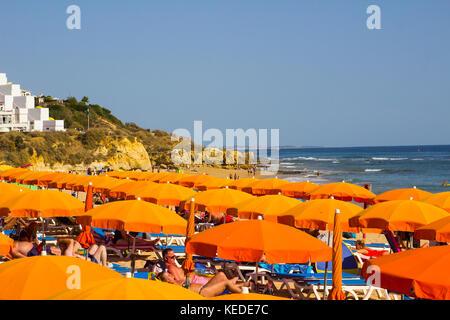 Dozens of brightly coloured sun beds and beach umbrellas on the sandy Praia Da Oura beach in Alubferia in Portugal - Stock Photo