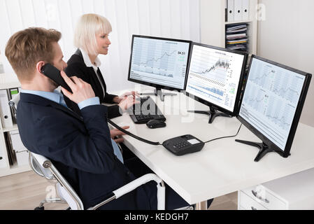 Two Businesspeople Analyzing Stock Charts On Multiple Computer Screens - Stock Photo