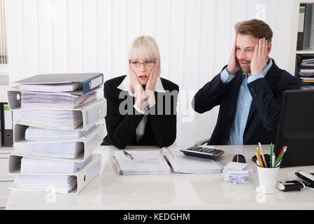 Stressed Young Businesspeople Looking At Stack Of Folders In Office - Stock Photo