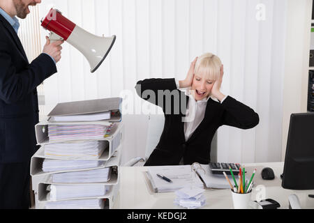 Boss Shouting At Young Businesswoman Through Loudspeaker In Office - Stock Photo