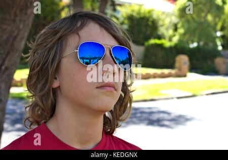 Young teenage male wearing blue sunglasses head shot against suburban background. - Stock Photo