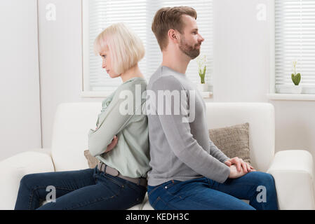 Young Unhappy Couple Sitting Back To Back On Couch At Home - Stock Photo
