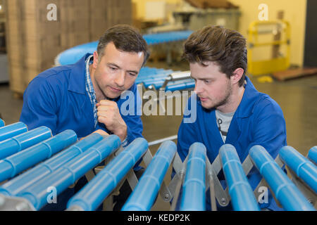 workers at a plastic pipes of factory - Stock Photo