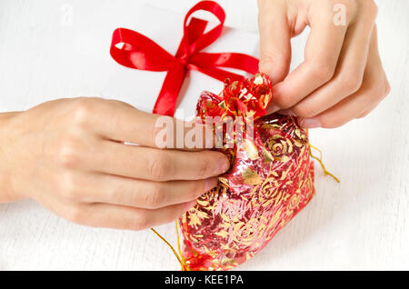 Women's hands tie a small bag with gifts, next to a gift box on the table. White background. - Stock Photo