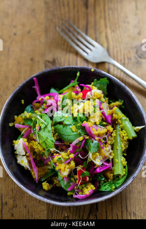 Turmeric infused quinoa with pickled red cabbage, radishes, spinach and peppers - Stock Photo