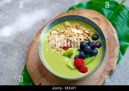 Green matcha smoothie with blueberries, raspberries and kiwi - Stock Photo