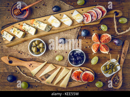 platter of italian cheeses with figs, olives, grapes and honey toned - Stock Photo