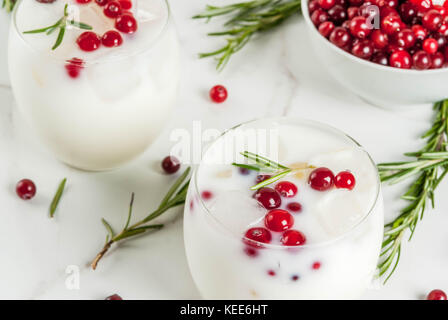 Ideas for drinks for Xmas and thanksgiving. White christmas margarita punch with cranberries and rosemary, on a - Stock Photo