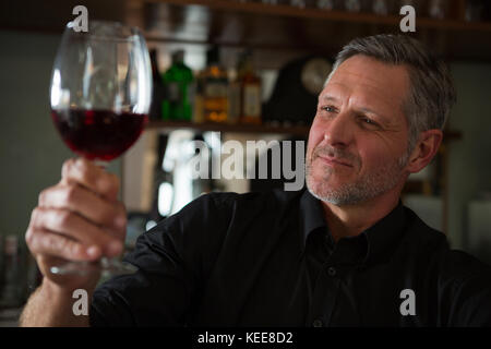 Close-Up of waiter looking at a glass of wine in restaurant - Stock Photo