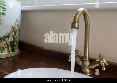 Close-up of water running through faucet in kitchen - Stock Photo