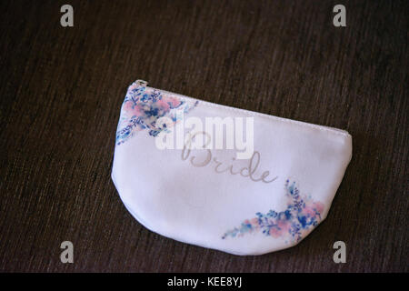 Delicate accessory with floral elements, a bridal purse with embroidered word 'Bride' in the front, against a dark - Stock Photo
