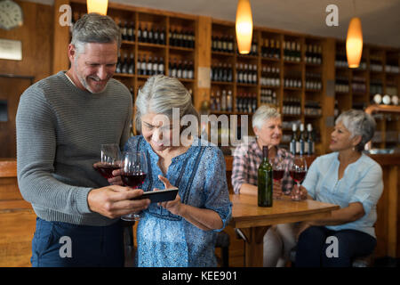 Senior couple looking their photos on mobile phone in restaurant - Stock Photo