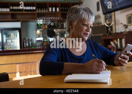 Waitress using her mobilephone near cafe counter - Stock Photo